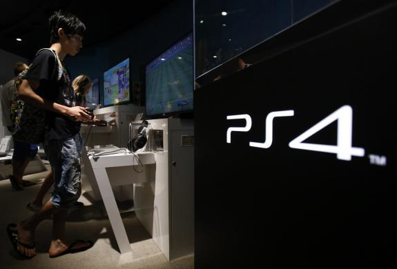 A man plays a video game on Sony Corp's Play Station 4 console at its showroom in Tokyo