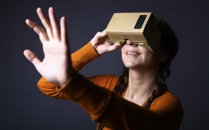 Color shot of a young woman looking through a cardboard, a device with which one can experience virtual reality on a mobile phone.; Shutterstock ID 258534815; user id: 13274325; user email: ken@ifanr.com; user_country: China; discount: 38%