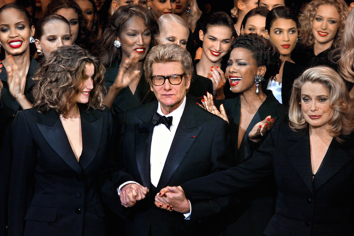 PARIS, FRANCE:  French designer Yves Saint-Laurent (C) salutes the crowd with French model Laetitia Casta (L) and French actress Catherine Deneuve (R) at the Centre Georges Pompidou art gallery in Paris, where the last Haute-Couture show ever of the designer took place. Hours before unveiling his last collection, innovative designer Yves Saint-Laurent said his love affair with women was not over and hinted he had other cards up his sleeve. (Photo credit should read JEAN-PIERRE MULLER/AFP/Getty Images)