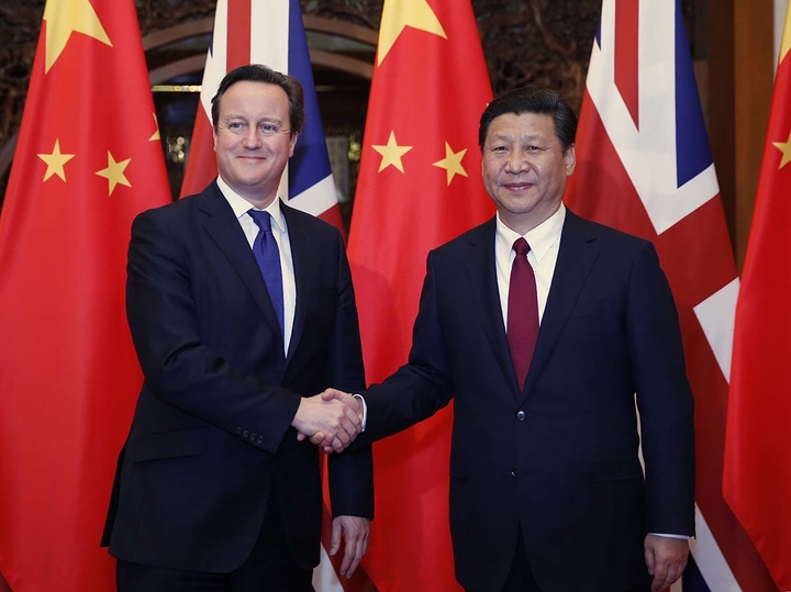 China's President Xi Jinping (R) shakes hands with Britain's Prime Minister David Cameron in front of Chinese and British flags during a meeting at Diaoyutai State Guesthouse in Beijing December 2, 2013. REUTERS/Ju Peng/Xinhua (CHINA - Tags: POLITICS BUSINESS) ATTENTION EDITORS - THIS IMAGE WAS PROVIDED BY A THIRD PARTY. FOR EDITORIAL USE ONLY. NOT FOR SALE FOR MARKETING OR ADVERTISING CAMPAIGNS. NO SALES. NO ARCHIVES.THIS PICTURE IS DISTRIBUTED EXACTLY AS RECEIVED BY REUTERS, AS A SERVICE TO CLIENTS.  CHINA OUT. NO COMMERCIAL OR EDITORIAL SALES IN CHINA. YES
