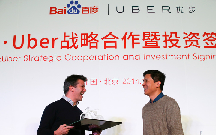 Uber CEO Kalanick smiles after receiving a gift from Baidu Inc. Chairman and CEO Li during the Baidu and Uber strategic cooperation and investment signing ceremony in Beijing