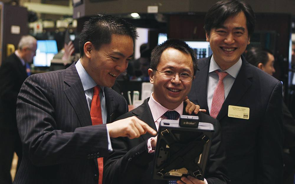 Hongyi Zhou takes a look at a trader's handheld trading device on the floor of the New York Stock Exchange before the company's Initial Public Offering (IPO) in New York