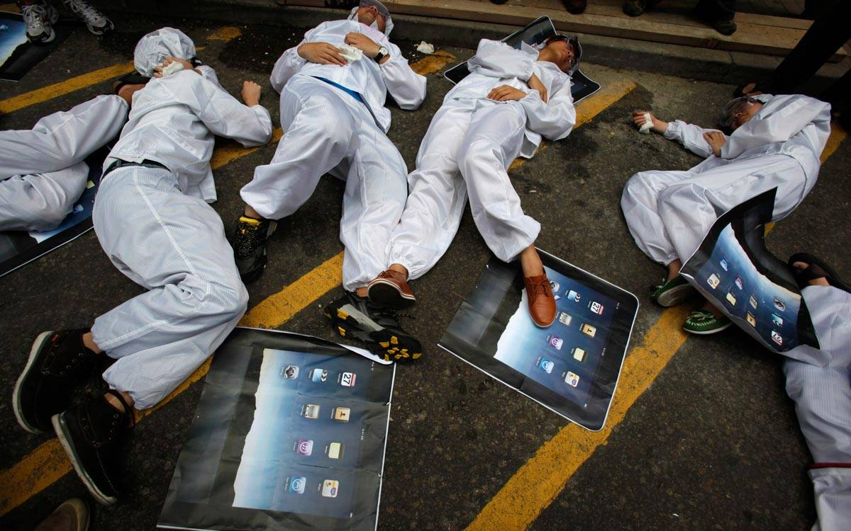 Chinese university students, in the role of Foxconn workers, lie on the floor during a street drama in Hong Kong