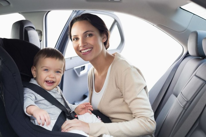 36446810 - mother securing her baby in the car seat in her car