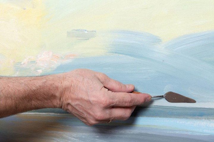 52593289 - an artist's hand painting with a palette knife in studio
