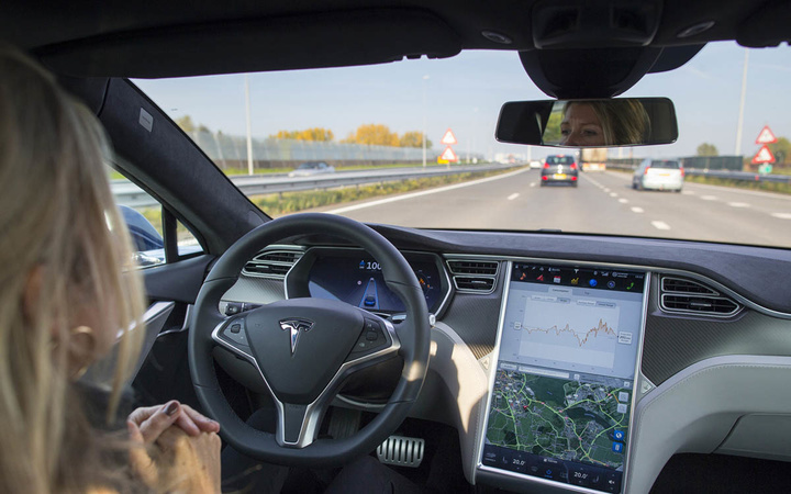 An employee drives a Tesla Motors Inc. Model S electric automobile, equipped with Autopilot hardware and software, hands-free on a highway in Amsterdam, Netherlands, on Monday, Oct. 27, 2015. Tesla started equipping the Model S with hardware -- radar, a forward-looking camera, 12 long-range sensors, GPS -- to enable the autopilot features about a year ago. Photographer: Jasper Juinen/Bloomberg