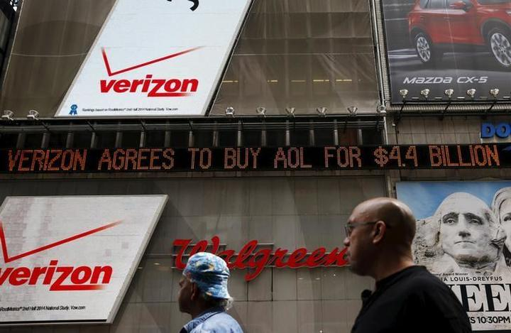 People walk by the Dow Jones electronic ticker at Times Square in New York,