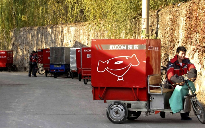 Chen Honglei, a 26-year-old courier of Jingdong, also known as JD.com, prepares his electric tricycle before leaving the company's Haidian district delivery station in Beijing, November 20, 2013. The Beijing-based firm, China's second largest e-commerce company, operates its own network of couriers and warehouses, a factor it says ensures timely and efficient delivery. Larger rivals Tmall and Taobao, the online marketplaces run by mega-firm Alibaba Group Holding Ltd, still depend on merchants and external courier firms for their logistics. Jingdong uses a 10,000-strong fleet of couriers to deliver packages to major locations across China within 24 hours. The company also has 1,400 warehouses nationwide to supply a customer base that accounts for over a sixth of China's 591 million registered Internet users. Picture taken November 20, 2013. REUTERS/Paul Carsten (CHINA - Tags: BUSINESS EMPLOYMENT SCIENCE TECHNOLOGY)